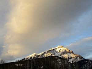 The snow-capped Cascade Mountain turning golden in the setting sun