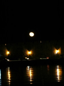 The moon rises above the town walls along the harbourtside