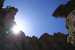 The sun peeping over the top of towering crags