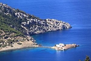 Looking down from the shoulder of the hill to Skoumisa Bay and the island monastery of Agios Emilianos
