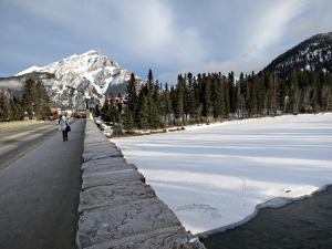 Looking across the town bridge built in 1923, Cascade Mountain at the end of Banff Avenue, the Bow River partly snow covered,partly flowing water