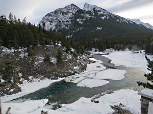 More open water than usual in winter below the falls seen from the top of the crag alongside, Mount Rundle towering above