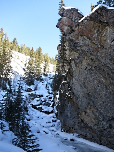 """a vertical rock face towered on the right, narrow ledges picked out in white"""