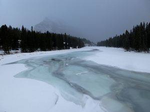 Newly frozen surface on the Bow River, Mountain Rundle lost in the snow sweeping down the valley