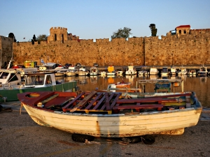 The sun warms the stone walls, reflections of small fishing boats in the mirror-smooth water