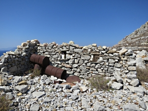 Ruins of house with ornamental oil drums