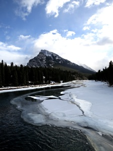 Looking downstream from the new footbridge over the Bow River towards Mount Rundle, more open water than usual, ice breaking up