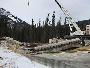 Bridge gone, derailed wagon left across the creek to dam it