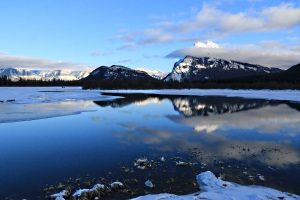 The pond drains into the lake creating a broad open channel in the ice, the flat-calm water reflecting Mount Rundle and the diminutive Tunnel Mountain