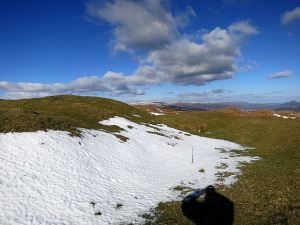 Snow ablated by sun and wind, small cumulus cloud marking the curving edge of the ridge