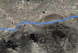 the enclosure is just above the blue track on the satellite image between the two areas of distinctly flat ground.