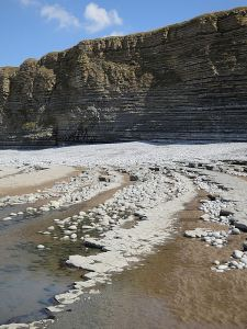 Sequence of dipping rock strata, pebbles and sand curving towards the cliffs