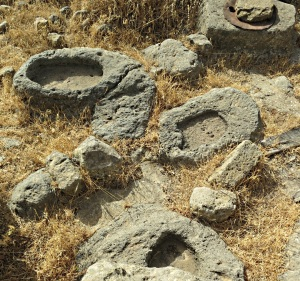 A scatter of carved stone bowls and the top of a cistern alongside.