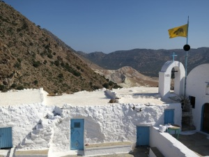 View across the courtyard of Agios Stavros monastery, the top of the Alexandros crater just beyond, Stephanos out of sight below