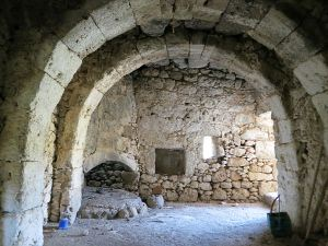 Barrel-arched construction with a fireplace in the corner and pestle and mortar beside it