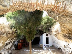 The underground church with the remnant of the arched terracotta roof and the cave with the thermal spring in the background
